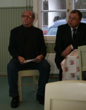 Kuva 2: Luvian Karjalaseuran varapuheenjohtaja Pauli Sihvonen (vasemmalla) ja Rauman Karjalaisten puheenjohtaja Juha Pökkönen seuraavat silmät ja korvat tarkkoina Pekka Peren esitystä.