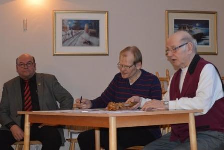 Kuva 1: Kuvassa oikealla kokouksen puheenjohtaja Toivo Hannukainen, keskellä sihteeri Raimo Hannukainen. Vasemmalla kokouksen edistymistä tarkkailee Karjalaseurojen Satakunnan piirin puheenjohtaja Jouko Hämäläinen. (Kuva: Vesa Rouvali)
