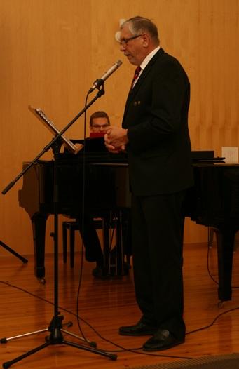 Kuva 3: Tilaisuuden juontajana toiminut Huittisten Karjalaseuran puheenjohtaja Heikki Kiiski osoitti olevansa monitaituri ja lauloi itse kaksi laulua, joilla oli ajatuksellinen yhteys Vpl. Pyhäjärveen. Säestäjänä toiminut Petri Kiiski lienee perinyt musikaalisuuden isältään.