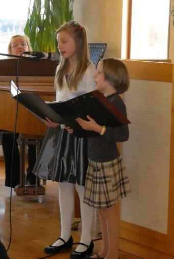 Kuva 3: Karoliina Jaakola (kuvassa vasemmalla) ja Milla Kaistamo lauloivat itsensä kuulijoiden sydämiin. Taustalla säestäjänä toiminut kanttori Elisa Hänninen. Kuvan on ottanut Tuija Kaasalainen.