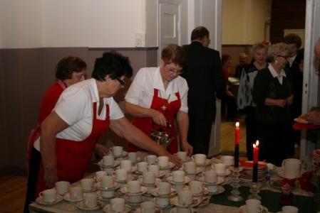 Kuva 10:  Juhliin osallistuvan yleisön viihtyvyyden kannalta tärkeät henkilöt unohtuvat usein eivätkä he saa sitä arvostusta, joka heille kuuluu. Tietovisan voittaja Airi Vihavainen (kuvassa keskellä) on jo ehtinyt palvelutehtävään ja tarttunut kahvipannun kahvaan.