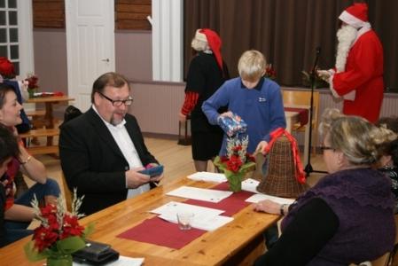 """Kuva 16: Seppo Kaljunen on jo saanut lahjansa. Pukin """"lapsityövoima"""" jatkaa lahjojen jakokierrosta."""