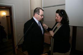 Kuva 2: Toiminnanjohtaja Satu Hallenberg kiinnitti ansiomerkin Pekka Salosen takin rintamukseen