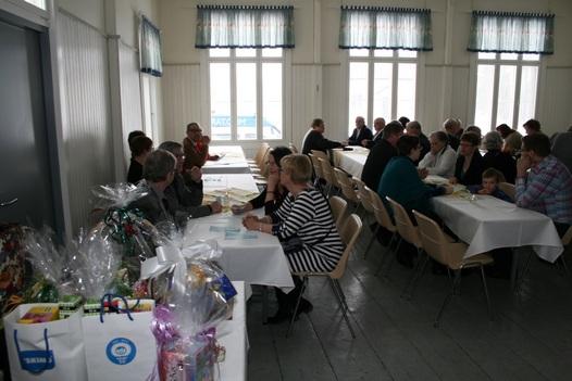Kuva 1: Muutama hetki ennen tilaisuuden alkamista, mm. yhtä bussilastillista ruokailijoita vielä odotellaan. Vasemmalla edessä osa runsasta arvontapalkintopöytää.