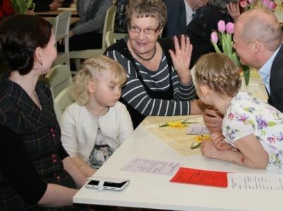 Kuva 1: Ella ja Emilia Lehtola yhdessä vanhempiensa ja Hiitolan Pitäjäseuran sihteerin Tuula Merran kanssa ennen esiintymisvuoron alkua