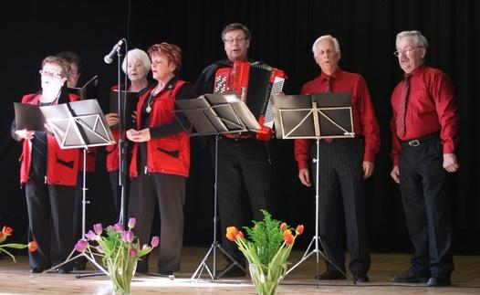 Kuva 8: Lauluyhtye Evakot esitti karjalaishenkisiä lauluja ja laulatti yleisöä. Evakoissa laulavat Milja Peltomaa, Sinikka Rajainmäki, Terttu Ketola, Raija Laaksonen, Tarmo Peltomaa (soittaa samalla haitaria) Veijo Sinkkonen ja Viljo Ylönen.