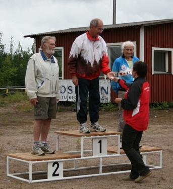 Kuva 5: Kilpailun vanhimmat osanottajat olivat sarjassa H80. Ikinuori Erkki Lätti (Forssan Seudun Karjalaseura) ottaa vastaan kultamitalin ja onnittelut palkintoja jakaneen Päivi Klemelän kädestä. Vasemmalla hopealle sijoittunut Kauko Kimpimäki (Valamo-Seura)ja oikealla pronssimitalisti Eino Engvist (Jämsän Karjala-Seura).