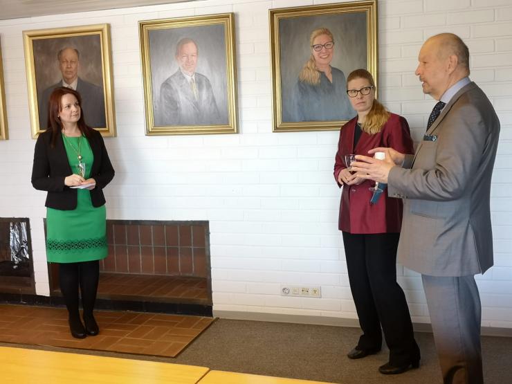 Karjalan Liiton puheenjohtaja Outi Örn, Marjo Matikainen-Kallström ja Markku Laukkanen puheejohtajien muotokuvien äärellä. Kuvassa on myös Rauno Merion muotokuva. Kuva Mervi Piipponen.